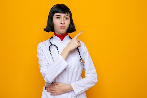 청진기가 옆을 가리키고 배에 손을 대고 있는 의사 유니폼을 입은 자신감 있는 젊은 백인 여성