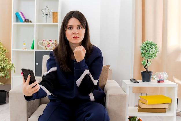 自信を持って若いかなり白人女性は、拳を探して携帯電話を握り締めて設計されたリビングルームの肘掛け椅子に座っています