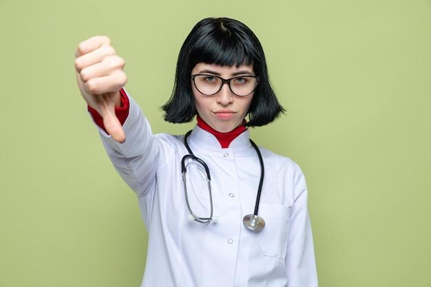 Fiduciosa giovane donna abbastanza caucasica con gli occhiali in uniforme da medico con stetoscopio che guarda verso il basso