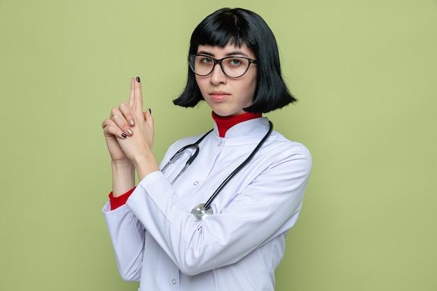 両手で聴診器ジェスチャー銃と医者の制服を着た眼鏡をかけた自信を持って若いかなり白人女性