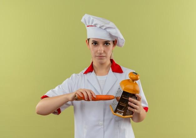 Fiducioso giovane bella cuoca in uniforme da chef che grattugia la carota con la grattugia isolata sulla parete verde