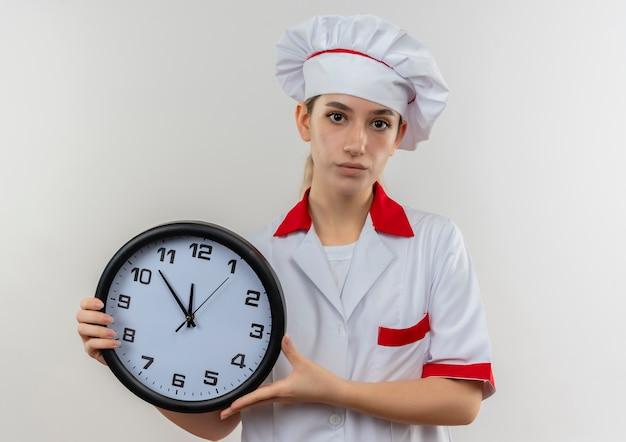 Fiducioso giovane bella cuoca in uniforme da chef che tiene l'orologio isolato su parete bianca