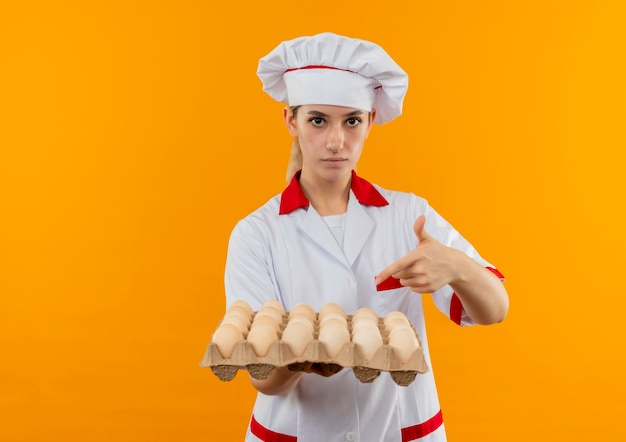 Confident young pretty cook in chef uniform holding and pointing at carton of eggs isolated on orange wall with copy space