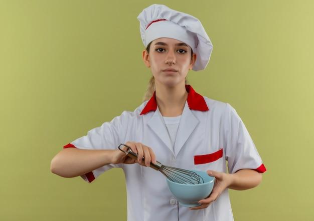 Fiducioso giovane e grazioso cuoco in uniforme da chef che tiene in mano una frusta e una ciotola isolate sul muro verde