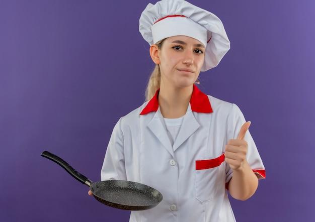 シェフの制服を着た自信に満ちた若いきれいな料理人がフライパンを持ち、紫色の壁に孤立した親指を現す