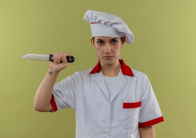 緑の壁に分離されたナイフを持ったシェフの制服を着た自信のある若いきれいな料理人