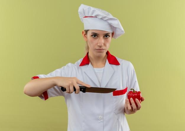 シェフの制服を着た自信に満ちた若いきれいな料理人がコショウを持ち、緑の壁にナイフでそれを指している