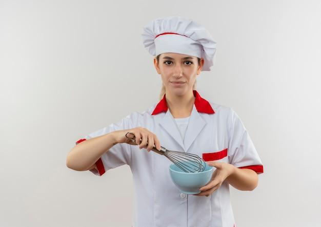 白い壁に分離された泡立て器とボウルを保持しているシェフの制服を着た自信のある若いきれいな料理人
