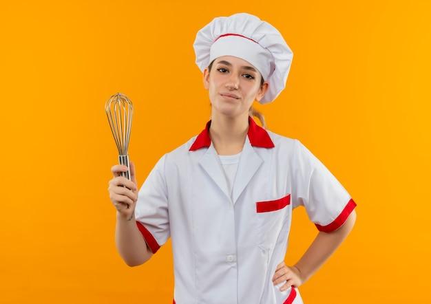 オレンジ色の壁に分離された腰に手で泡立て器を保持しているシェフの制服を着た自信のある若いきれいな料理人
