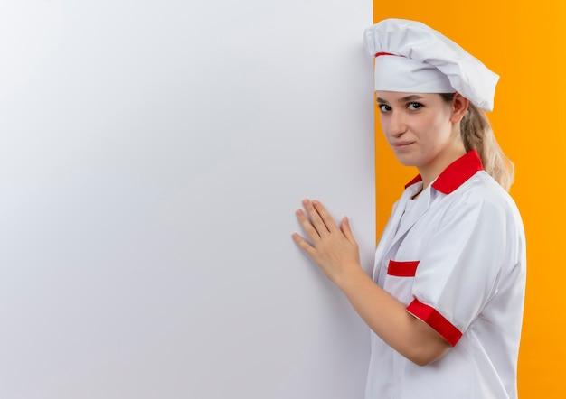 シェフの制服を着た自信のある若いきれいな料理人が近くに立ち、白い壁にコピー スペースで隔離された白い壁に手を置きます