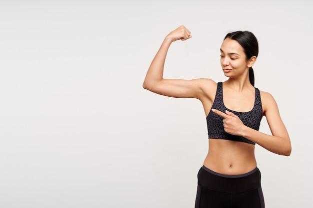 Уверенная в себе молодая довольно темноволосая женщина в спортивной одежде скручивает рот, глядя на свою сильную руку и показывая на нее указательным пальцем, позирует над белой стеной