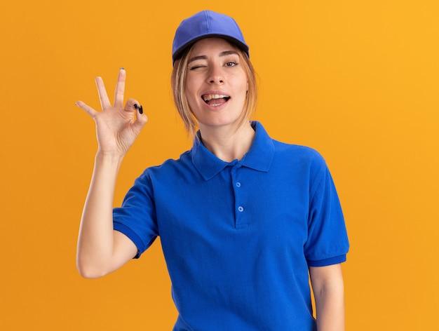 제복을 입은 자신감이 젊은 예쁜 배달 소녀가 눈을 깜박이고 오렌지에 확인 손 기호를 표시합니다.