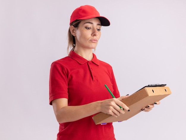 자신감이 젊은 예쁜 배달 소녀 유니폼을 보유하고 흰색 피자 상자에 클립 보드에 보이는