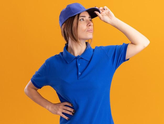 Уверенная молодая симпатичная доставщица в униформе кладет руку на кепку и смотрит в сторону на оранжевом Бесплатные Фотографии