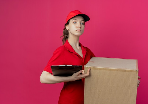 Confident young pretty delivery girl in red uniform and cap holding carton box and clipboard isolated on crimson background with copy space