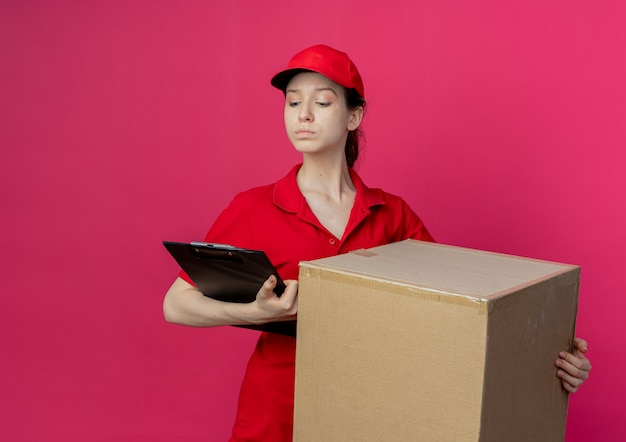 Confident young pretty delivery girl in red uniform and cap holding carton box and clipboard looking at clipboard isolated on crimson background with copy space