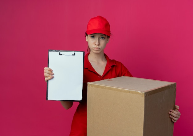 Confident young pretty delivery girl in red uniform and cap holding carton box and showing clipboard isolated on crimson background with copy space