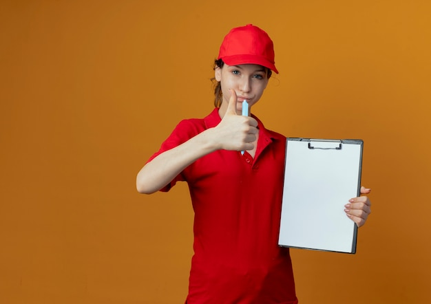 Confident young pretty delivery girl in red uniform and cap holding pen and clipboard and showing thumb up at camera isolated on orange background with copy space