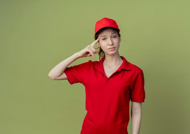 Fiduciosa giovane ragazza graziosa di consegna in uniforme rossa e cappuccio che mette il dito sul tempio isolato su priorità bassa verde oliva con lo spazio della copia