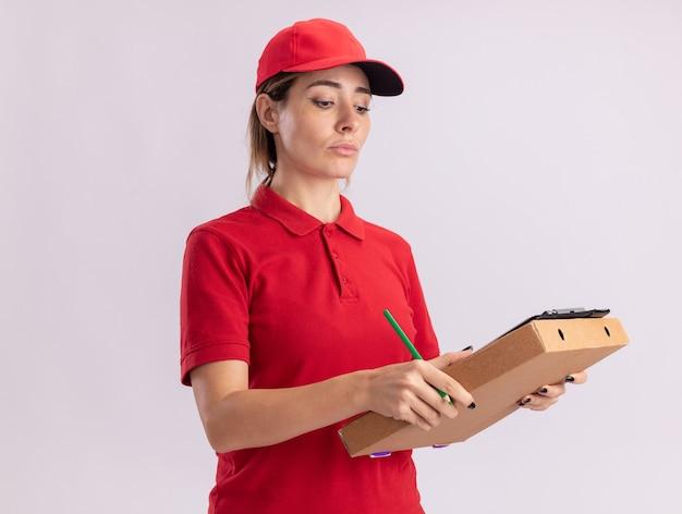 Fiduciosa giovane bella ragazza di consegna in uniforme tiene e guarda negli appunti sulla scatola della pizza su bianco