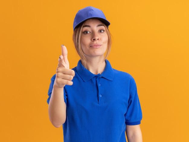 Fiduciosa giovane bella ragazza di consegna in punti uniformi alla telecamera su arancione