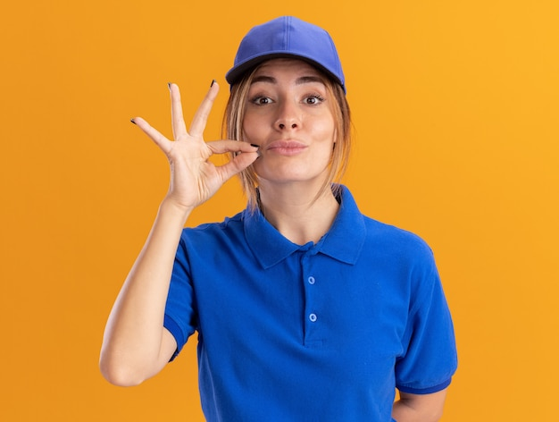 Confident young pretty delivery girl in uniform pretends to zip mouth on orange