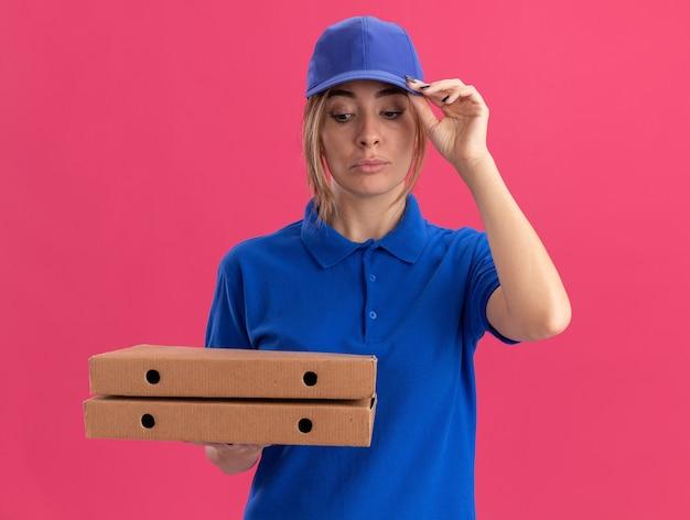 Fiduciosa giovane bella ragazza di consegna in uniforme mette la mano sul cappuccio e tiene le scatole per pizza sul rosa