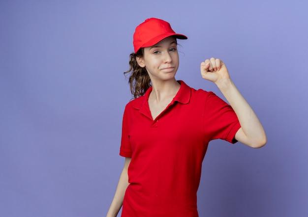 Уверенная молодая симпатичная доставщица в красной форме и кепке, показывающая поднятый кулак на фиолетовом фоне с копией пространства