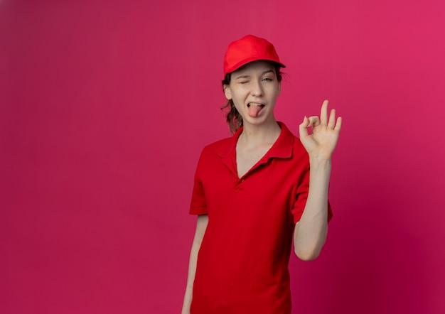 Fiducioso giovane bella ragazza di consegna che indossa l'uniforme rossa e cappello facendo segno ok ammiccante e mostrando la lingua isolata su sfondo cremisi con spazio di copia
