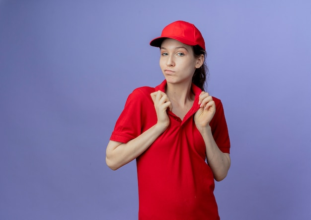 Fiduciosa giovane bella ragazza di consegna che indossa l'uniforme rossa e il cappuccio che afferra il colletto della sua maglietta isolato su sfondo viola con spazio di copia