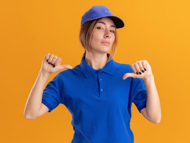 오렌지 벽에 고립 된 두 손으로 자신의 유니폼 포인트에 자신감이 젊은 예쁜 배달 여자