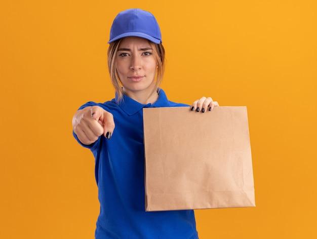 Fiduciosa giovane donna graziosa di consegna in uniforme tiene il pacchetto di carta e punti nella parte anteriore isolata sulla parete arancione