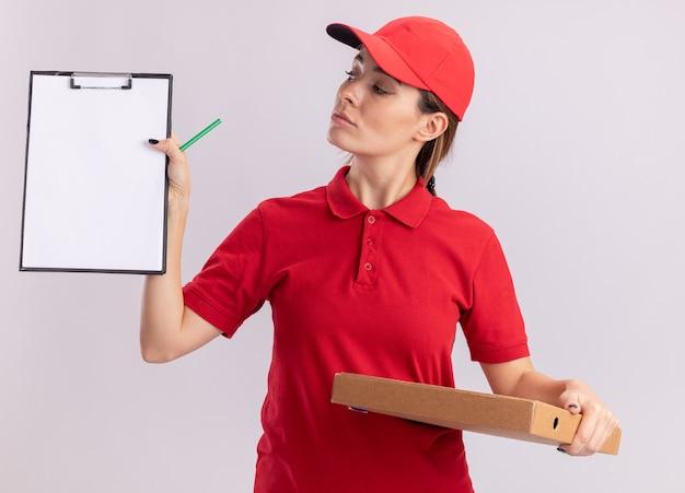 La giovane donna graziosa sicura di consegna in uniforme tiene la scatola della pizza ed esamina la lavagna per appunti isolata sulla parete bianca