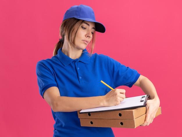 Fiduciosa giovane donna graziosa di consegna in uniforme tiene scatole di pizza e scrive negli appunti con la penna isolata sulla parete rosa