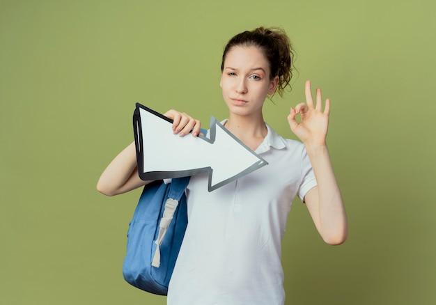 Уверенная молодая симпатичная студентка в сумке на спине, держащая стрелку, указывающую в сторону и делающая хорошо, знак на оливково-зеленом пространстве