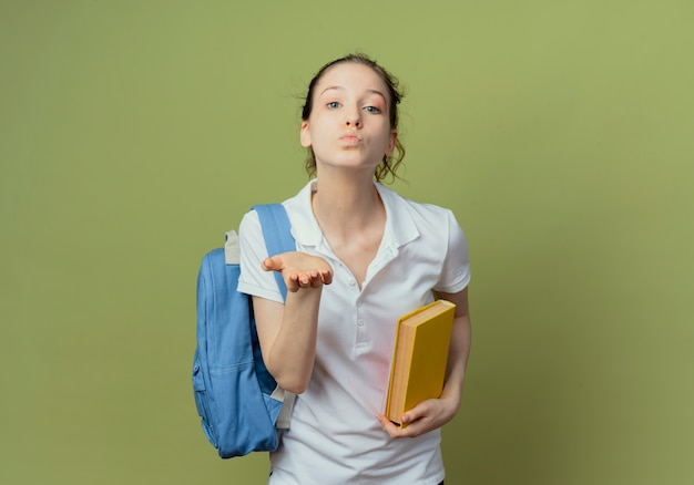 Уверенная молодая симпатичная студентка в задней сумке, держащая книгу и отправляющая воздушный поцелуй в камеру, изолированную на зеленом фоне с копией пространства