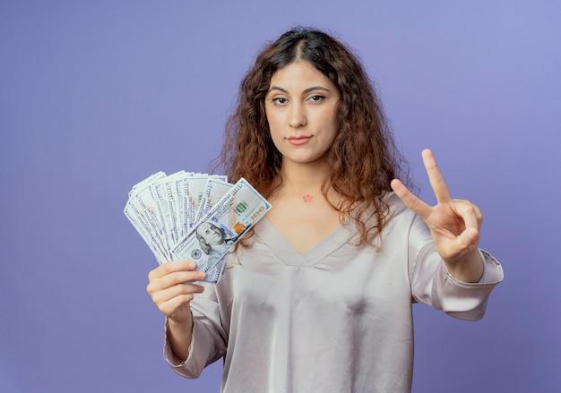 Giovane ragazza graziosa sicura che tiene contanti e che mostra la pace