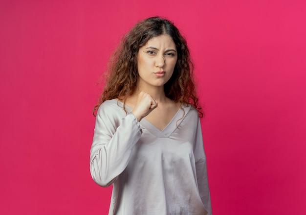 Fiducioso giovane bella ragazza alzando il pugno isolato sulla parete rosa