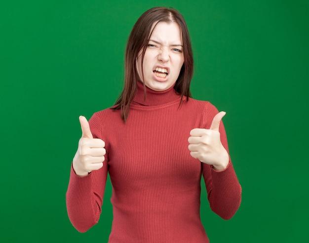 Fiducioso giovane bella ragazza che mostra i pollici in su isolato sulla parete verde