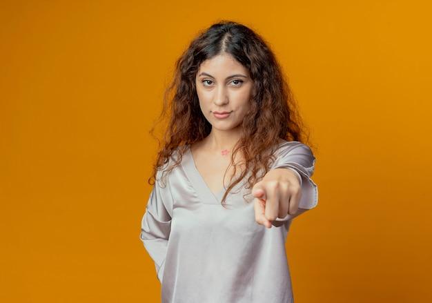 노란색 벽에 고립 된 제스처를 보여주는 자신감 젊은 예쁜 여자