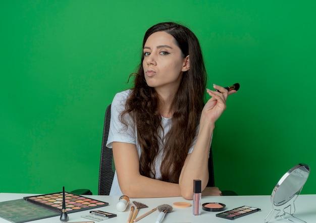 Уверенная молодая красивая девушка сидит за косметическим столом с инструментами для макияжа, держа кисть для румян, положив руку на стол, изолированный на зеленом фоне