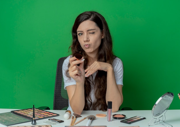 自信を持って若いかわいい女の子は、赤面ブラシウィンクを保持し、緑の背景に分離されたカメラを指して化粧ツールで化粧テーブルに座っています
