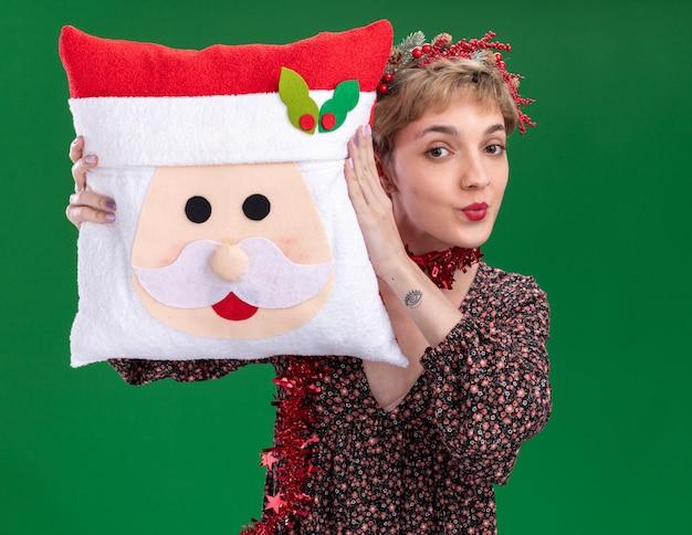 Уверенная в себе молодая красивая девушка в рождественском венке и гирлянде из мишуры на шее, держащая подушку санта-клауса, касаясь ею головы поджатыми губами, изолированными на зеленой стене