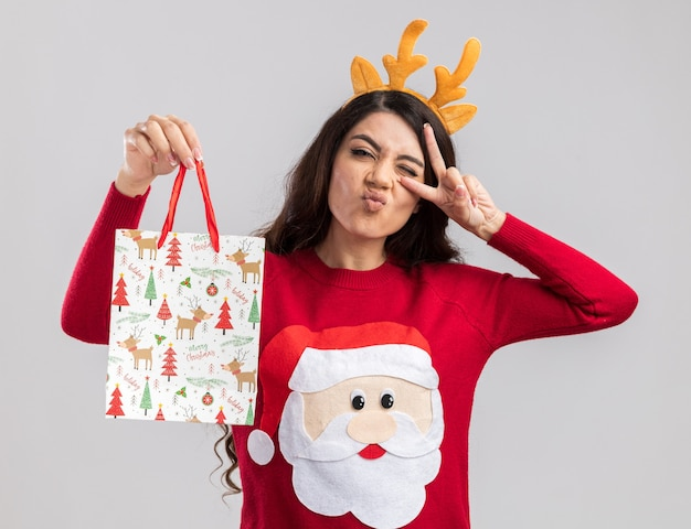 Уверенная молодая красивая девушка в головной повязке с оленьими рогами и свитере санта-клауса, держащая рождественский подарочный пакет, смотрит, показывая символ v-знака рядом с подмигивающими глазами