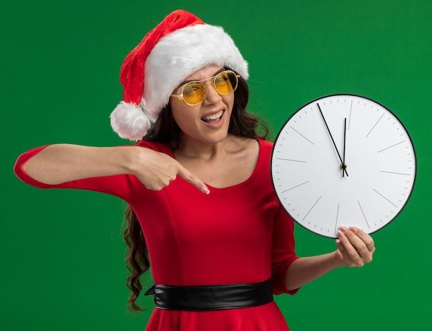 Уверенная молодая красивая девушка в шляпе санта-клауса и очках держит и указывает на часы, глядя в камеру, изолированную на зеленом фоне