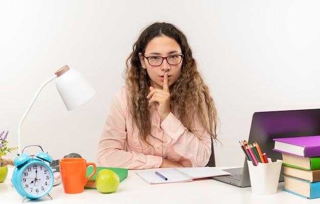 Уверенная молодая симпатичная школьница в очках сидит за столом со школьными инструментами, делает домашнее задание, жестикулируя тишину, изолированную на белом