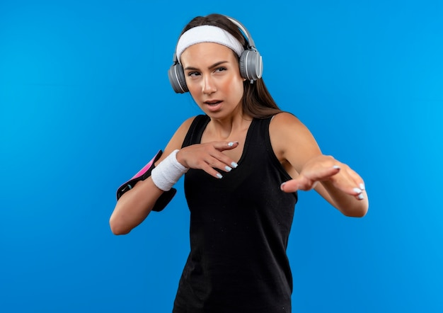 파란색 벽에 고립 된 측면을보고 손을 뻗어 전화 완장과 머리띠와 팔찌와 헤드폰을 착용 확신 젊은 꽤 스포티 한 소녀