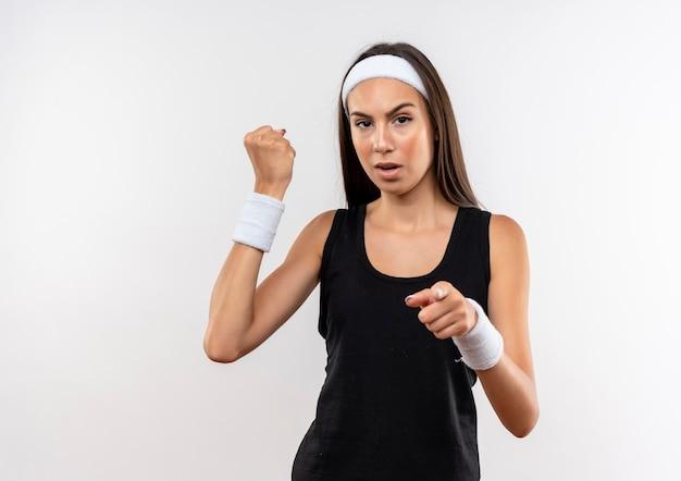 Уверенная молодая симпатичная спортивная девушка с головной повязкой и браслетом, сжимая кулак и указывая на белую стену с копией пространства