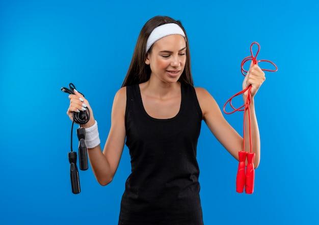 Уверенная молодая симпатичная спортивная девушка с головной повязкой и браслетом, держащая и смотрящая на скакалки на синей стене