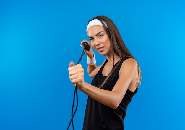 Уверенная молодая симпатичная спортивная девушка с повязкой на голову и браслетом, держащей и вытягивающей прыжки через скакалку, изолированную на синей стене с копией пространства